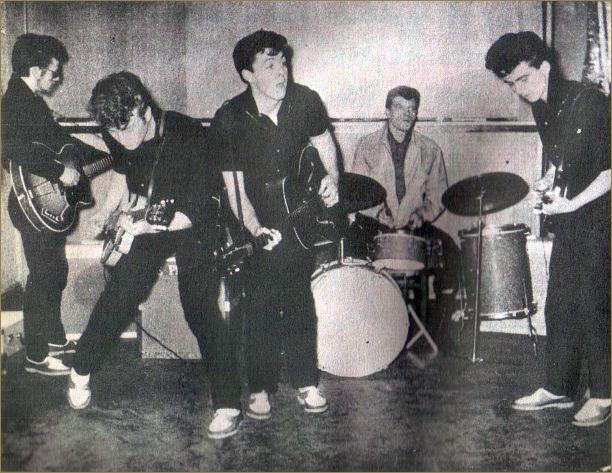 """Aqui os Silver Beatles, em seu primeiro compromisso profissional em 1960 para uma apresentação no Larry Parnes Show. Daqui também saiu a primeira turnée de 2 semanas como conjunto de acompanhamento pelo norte da Escócia. A esquerda está Stu Sutcliffe, recém chegado, que mal conseguia tocar o contra-baixo daí estar tentando ficar de costas para a plateia. John Lennon e Paul McCartney em primeiro plano, George Harrison a direita, e ao fundo o mal humorado baterista Johnny Hutch, """"caçado"""" de último minuto pois o conjunto estava sem baterista."""