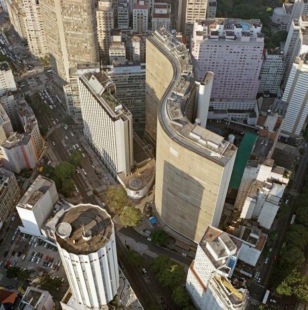 """A mega construção em """"S"""" ícone de turismo e um dos símbolos de São Paulo, tendo a sua frente um edifício menor atual sede do Bradesco em SP que era para ser um Hotel de luxo. Neste local existia a famosa Vila Normanda, removida para a construção do então intitulado Rockefeller Center de São Paulo. Talvez se fosse hoje com tantas leis e instituições de proteção de patrimônio, a vila seria preservada e o Copan com seu hotel não seriam construídos."""
